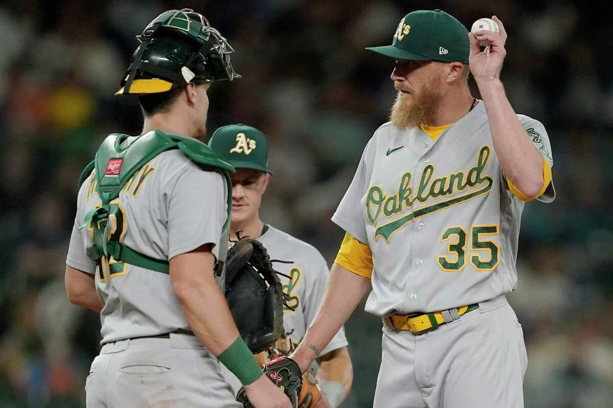 Oakland Athletics relief pitcher Jake Diekman (35) talks with catcher Sean Murphy, left, on the mound after a wild pitch from Diekman allowed Seattle Mariners' Dylan Moore to score with the score tied during the seventh inning of a baseball game Friday, July 23, 2021, in Seattle. (AP Photo/Ted S. Warren)