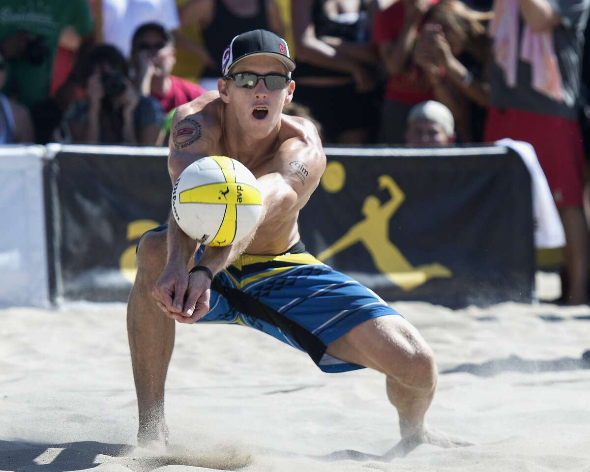 FILE - In this Sept. 21, 2014, file photo, Tri Bourne makes a dig as he and John Hyden played Casey Patterson and Jake Gibb during the AVP Championships beach volleyball match at Huntington Beach, Calif. American beach volleyball player Taylor Crabb is out of the Olympics after several positive COVID-19 tests, and Bourne will take his place as the partner of four-time Olympian Jake Gibb when the competition begins at Tokyo's Shiokaze Park this weekend. (Kyusung Gong/The Orange County Register, File)