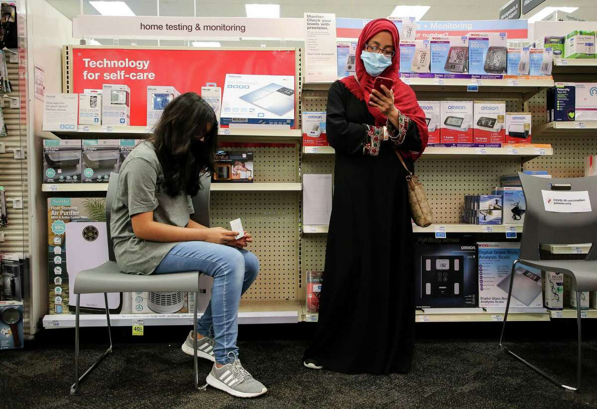 Arisha Amreen, 12, and her mother Ashma Binte Ahsan wait the 15 minutes recommended after she received a COVID-19 vaccine at a CVS on Thursday, July 22, 2021, in Sugar Land.