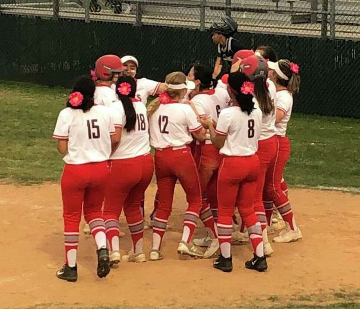 Travis softball players greet teammate Ariel Kowalewski after a home run during the 2021 season. Kowalewski was voted District 20-6A MVP after batting .657 with 13 home runs in 21 games.