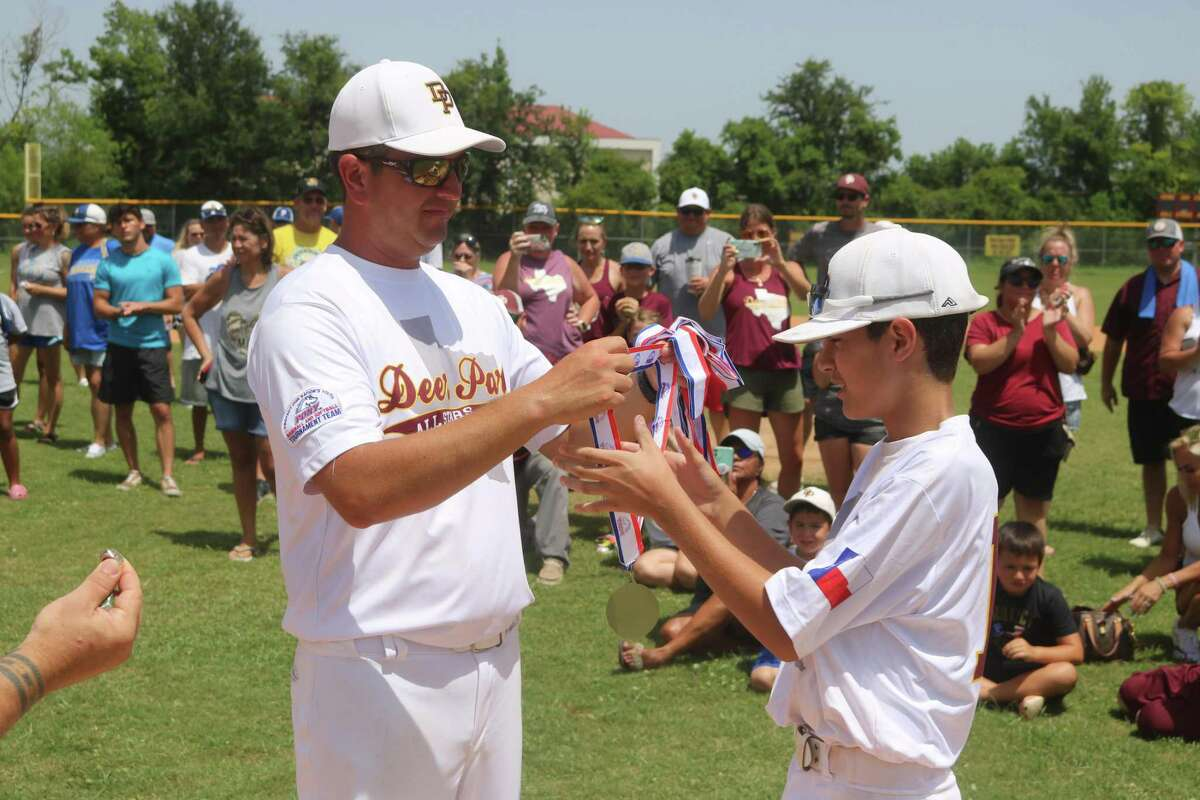Deer Park coach Ryan Kight presents a medal to winning pitcher Sam Jefferson during postgame festivities Saturday.