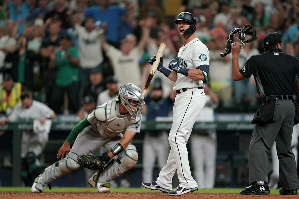 Seattle Mariners' Mitch Haniger yells as Oakland Athletics catcher Aramis Garcia moves to chase down a wild pitch in the ninth inning of a baseball game Saturday, July 24, 2021, in Seattle. Mariners' Jarred Kelenic scored from third and the Mariners won 5-4. (AP Photo/Ted S. Warren)