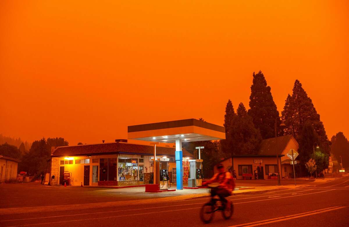 A man rides his bike past a gas station as smoke fills the sky during the Dixie fire in Greenville, California on July 23, 2021.