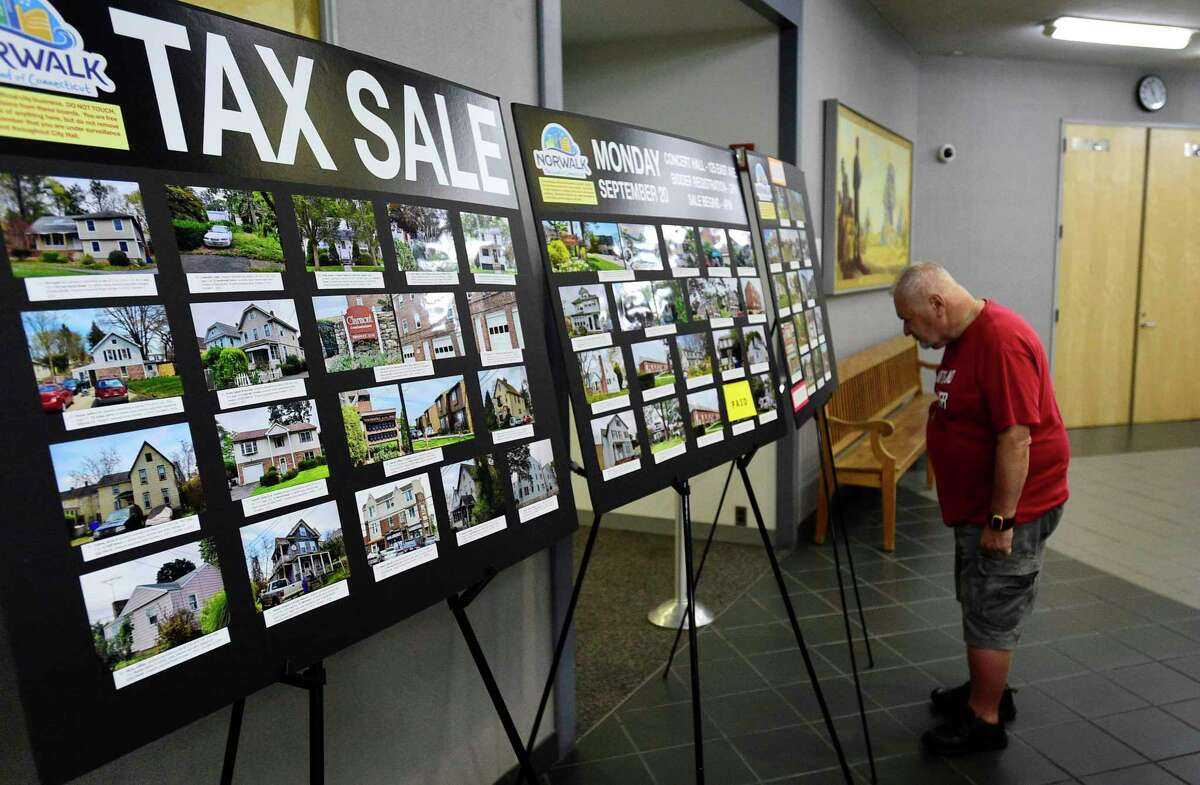 Residents look at the delinquent tax board at city hall Friday, July 23, 2021, in Norwalk, Conn. There will be a tax auction in September for owners do not pay.