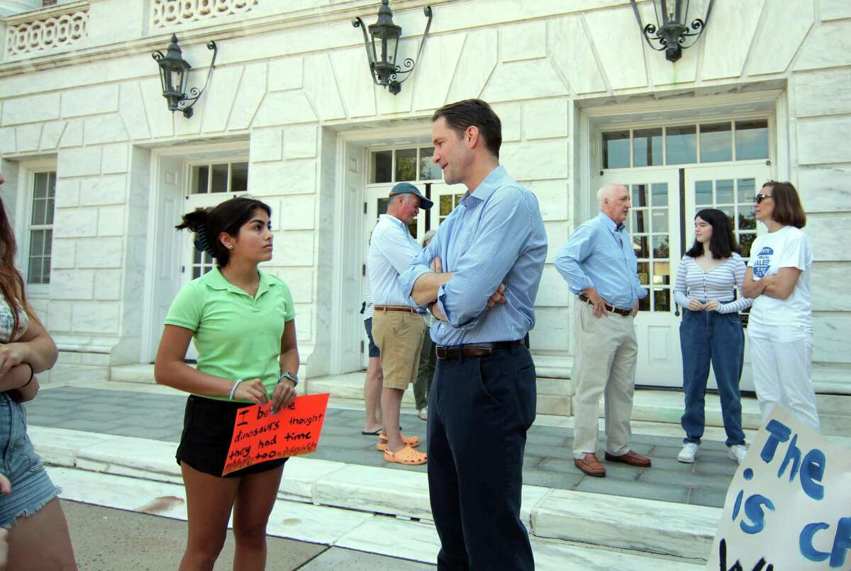 Congressman Jim Himes, center, speaks with Nina Gupte, co-founder and co-president with The Greenwich Environmental Advocacy Group (GEAG), a student-led local chapter of the environmental organization 350.org, during a climate change protest at Greenwich Town Hall in Greenwich, Conn., on Saturday July 24, 2021. The purpose of the protest is to get the town to pass a Climate Emergency Resolution.