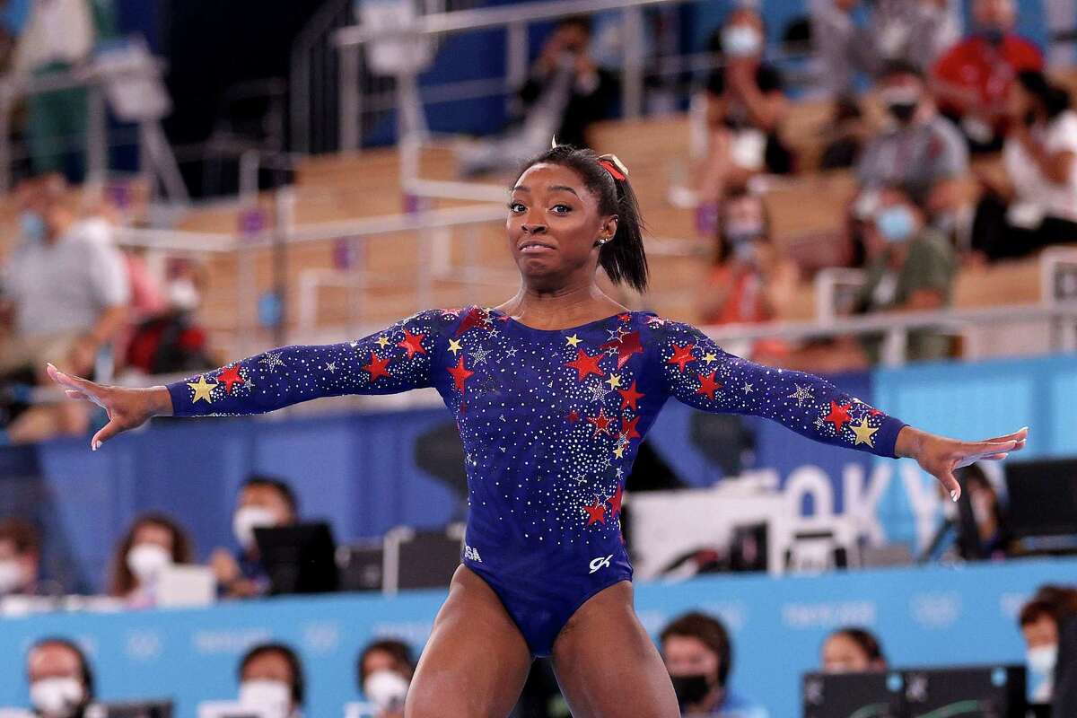 Simone Biles reacts after falling off the mat on her dismount from balance beam during women's gymnastics qualifications.