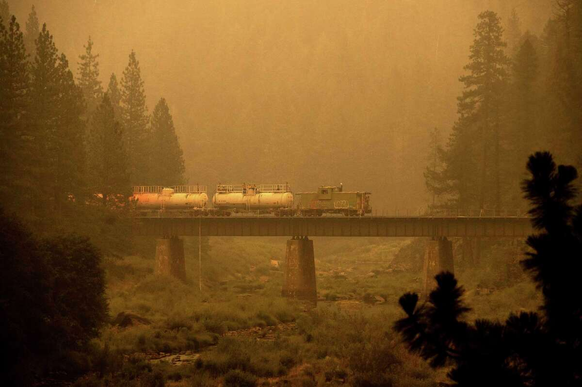 A fire train crosses a bridge Saturday as the Dixie Fire burns in Plumas County. The train is capable of spraying retardant to coat tracks and surrounding land. Smoke from the Dixie Fire spewed into the northern part of Lake Tahoe, bringing unhealthy air quality.