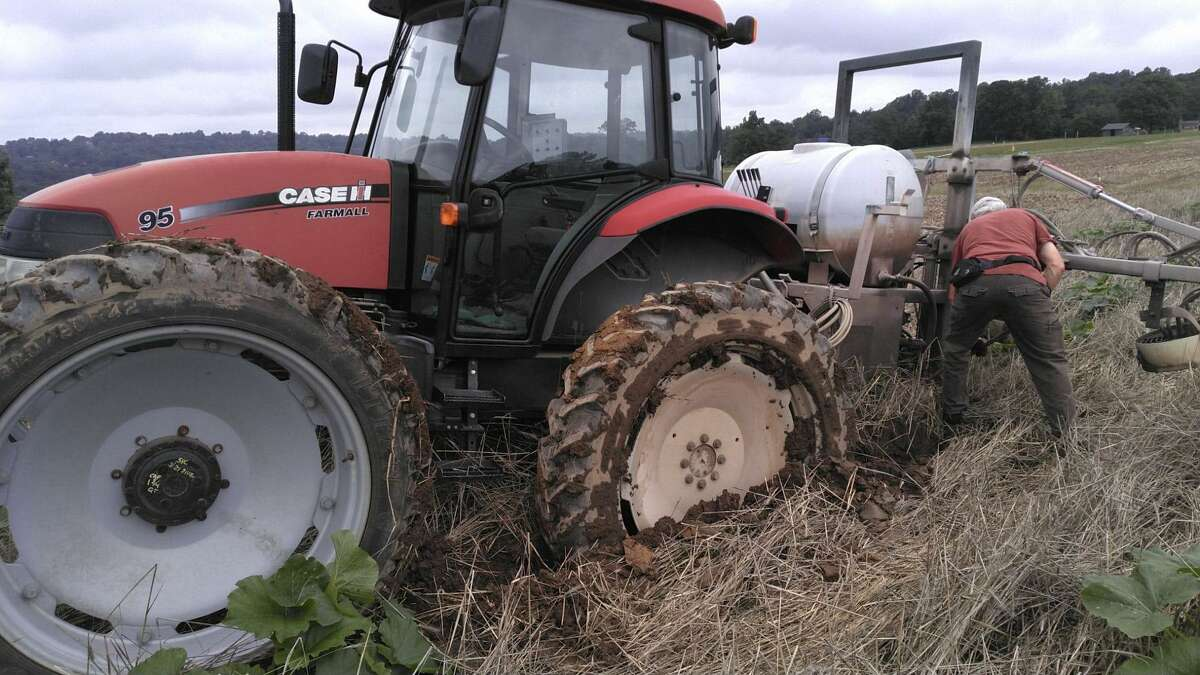 """After drought in May, the torrential rain that followed resulted in a tractor stuck in mud on the Jones Family Farm. """"In the middle of July to get a tractor stuck in a field - it's somewhat unheard of,"""" said Jamie Jones."""