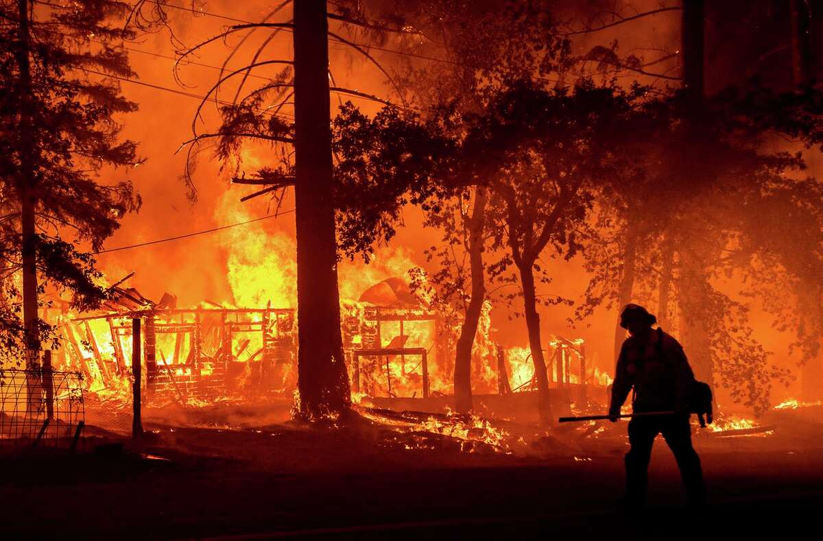 A firefighter passes a burning home July 24 as the Dixie Fire flares in Indian Falls (Plumas County).