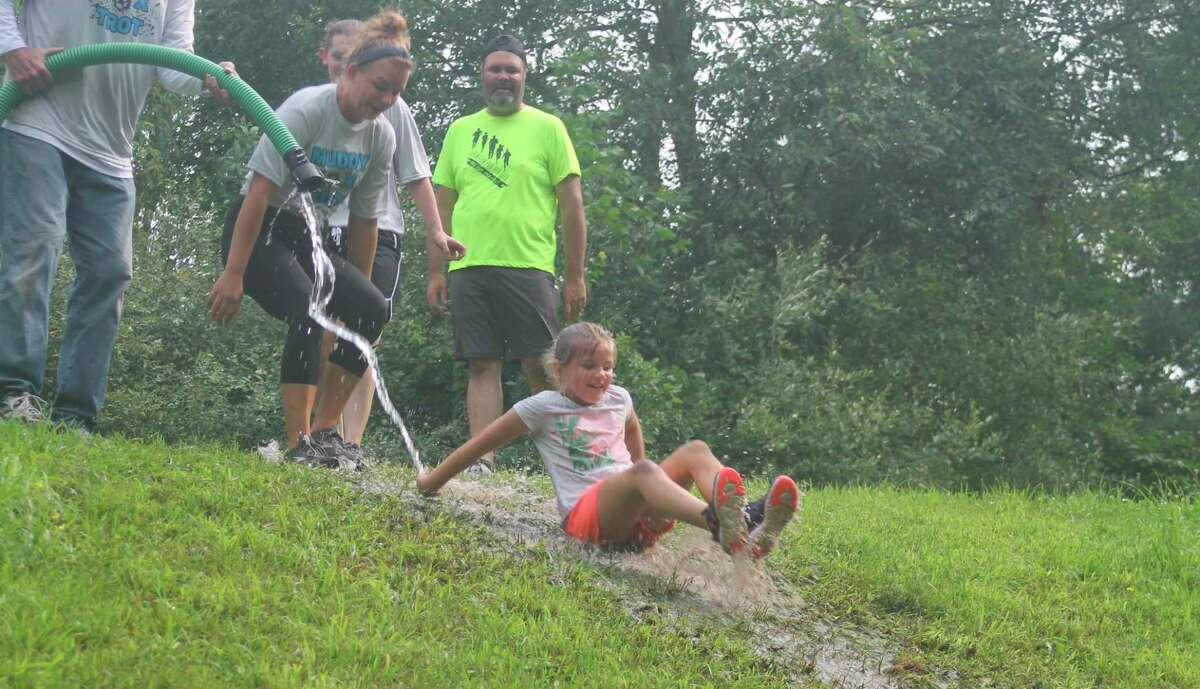 Runners slide down a muddy hill duringWest Shore Community College's Muddy Fox Trot 5K on the campus Saturday. The family friendly runraises money for theWSCC Foundation student scholarship fund. (Kyle Kotecki/News Advocate)