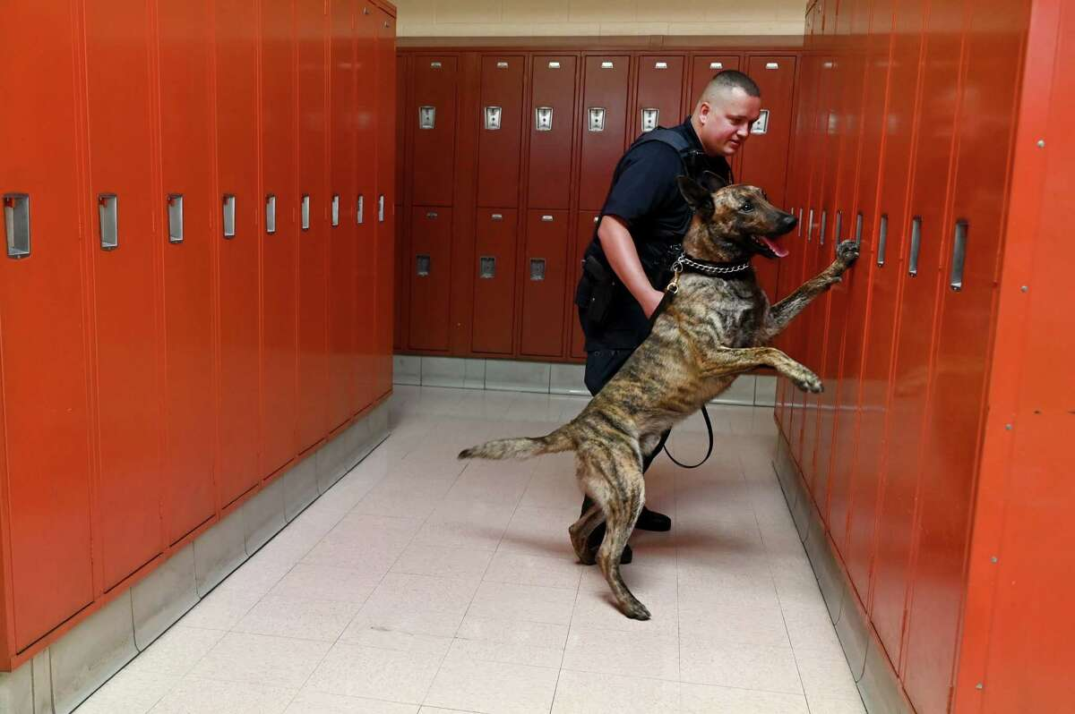 K-9 Police officer Anthony Roling leads Dexter through lockers at the Maryland Correctional Training Center to demonstrate how she has been trained to sniff out alcohol in prisons onJuly 23, 2021. in Hagerstown, Md.