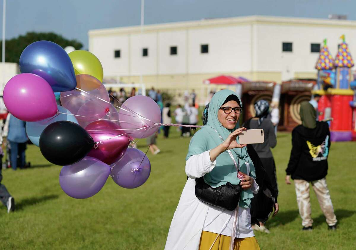 Maha Elnaggar takes photos while her children play during the Eid Carnival at the Muslim American Society Katy Center, 1800 Baker Rd., Saturday, July 24, 2021 in Houston.