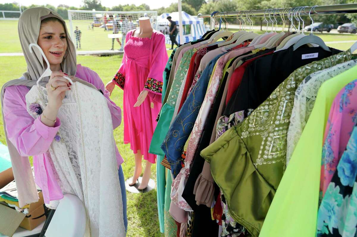 Shams Albayati displays clothing at the Embrohouse booth featuring designs by her and her sister, Sally Albayati, during the Eid Carnival at the Muslim American Society Katy Center, 1800 Baker Rd., Saturday, July 24, 2021 in Houston.