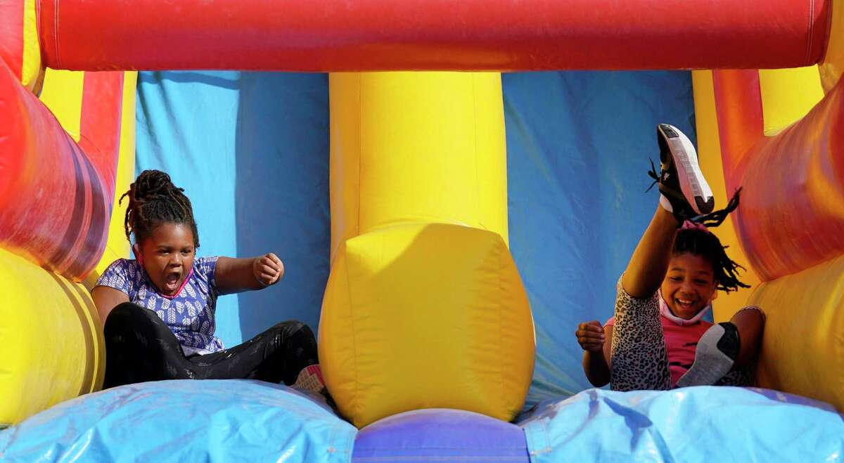 Zion Nash, 8, left, and her sister, Ashzia Nash, 10, right, play on an inflatable slide during the Eid Carnival at the Muslim American Society Katy Center, 1800 Baker Rd., Saturday, July 24, 2021 in Houston.