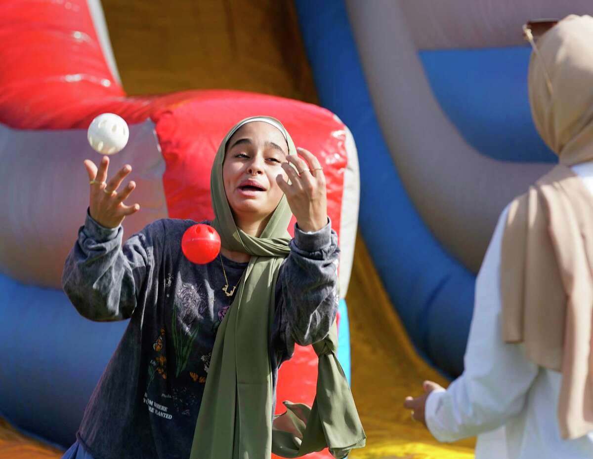 Aya Ahmed, left, attempts to juggle with Sarah Elbramwy, right, during the Eid Carnival at the Muslim American Society Katy Center, 1800 Baker Rd., Saturday, July 24, 2021 in Houston.
