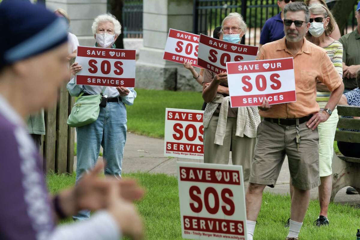 People gather for the SOS: Save Our Services Rally at Veteran's Park on Sunday, July 25, 2021, in Schenectady, N.Y. Those attending the rally say they have concerns about the loss of services that may result from the proposed merger of Ellis Medicine and Trinity Health, which is a Catholic heathcare system. (Paul Buckowski/Times Union)