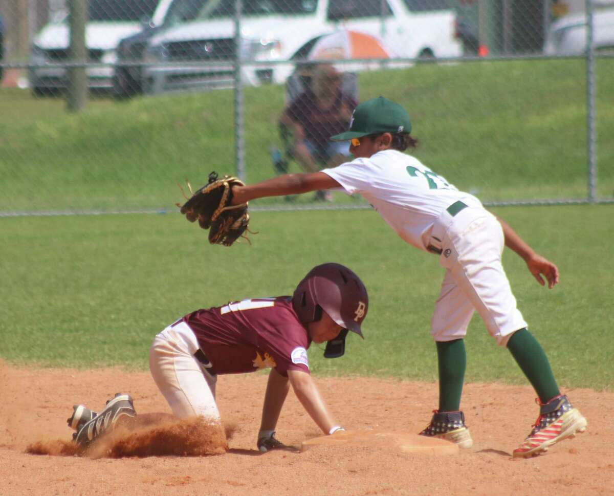 A Deer Park runner dives back to the second-base bag before the tag attempt during Saturday's South Zone semifinal game for the Mustang all-stars.