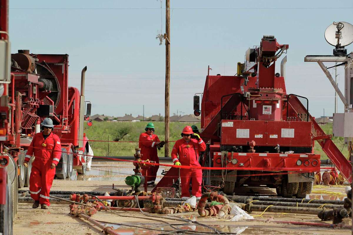In this file photo, Halliburton's employees work at a three wellhead fracking site in Midland in 2017. After a tough, pandemic-related downturn, the world's biggest oil field services companies expect their industry will enjoy a multi-year boom.