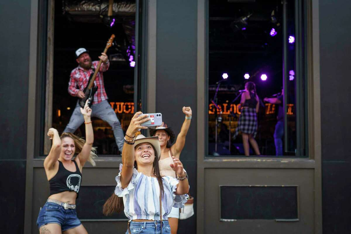 Kimberly Musarra of South Jersey gets a selfie with members of Tim Thurman's band in Nashville on Wednesday.