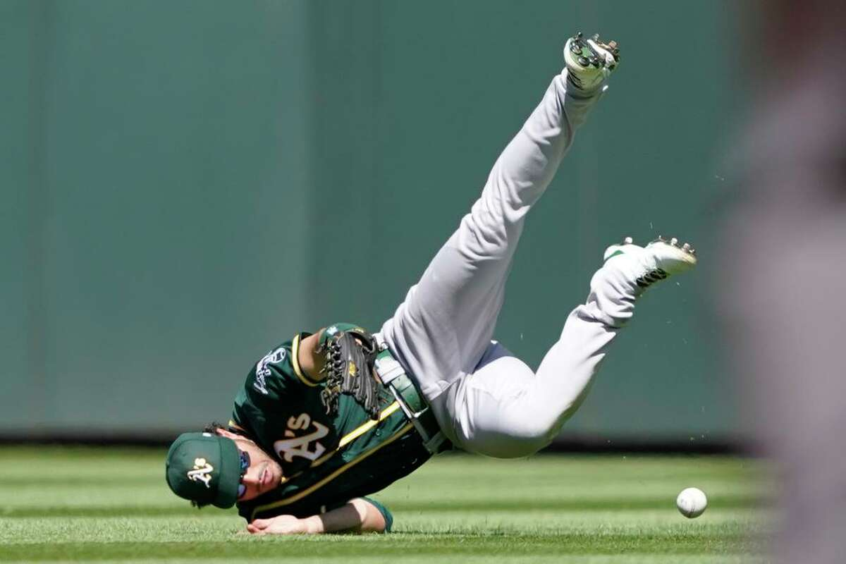 Oakland Athletics center fielder Ramon Laureano dives but can't get to an RBI single hit by Seattle Mariners' Tom Murphy during the third inning of a baseball game, Sunday, July 25, 2021, in Seattle. (AP Photo/Ted S. Warren)