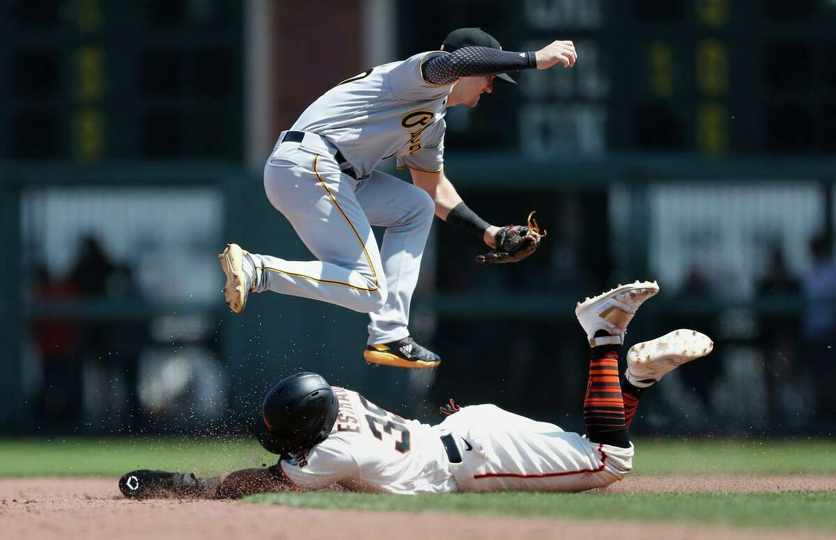Thairo Estrada of the Giants steals second base as Kevin Newman of the Pirates is unable to catch the throw from the catcher, allowing Steven Duggar to score in the bottom of the sixth.