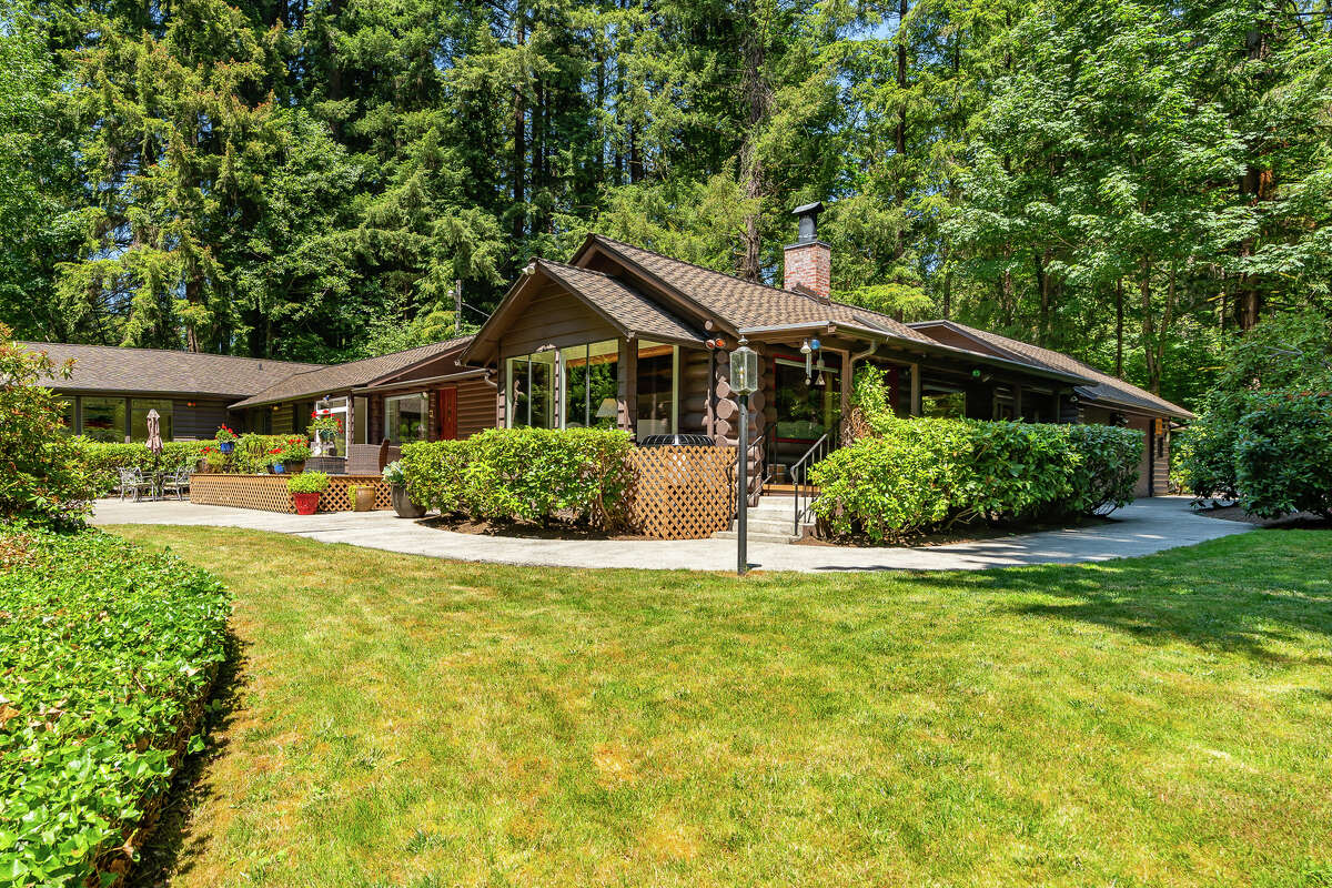 The home is set on a forested lot with plenty of level, cleared space for lawns and gardens.
