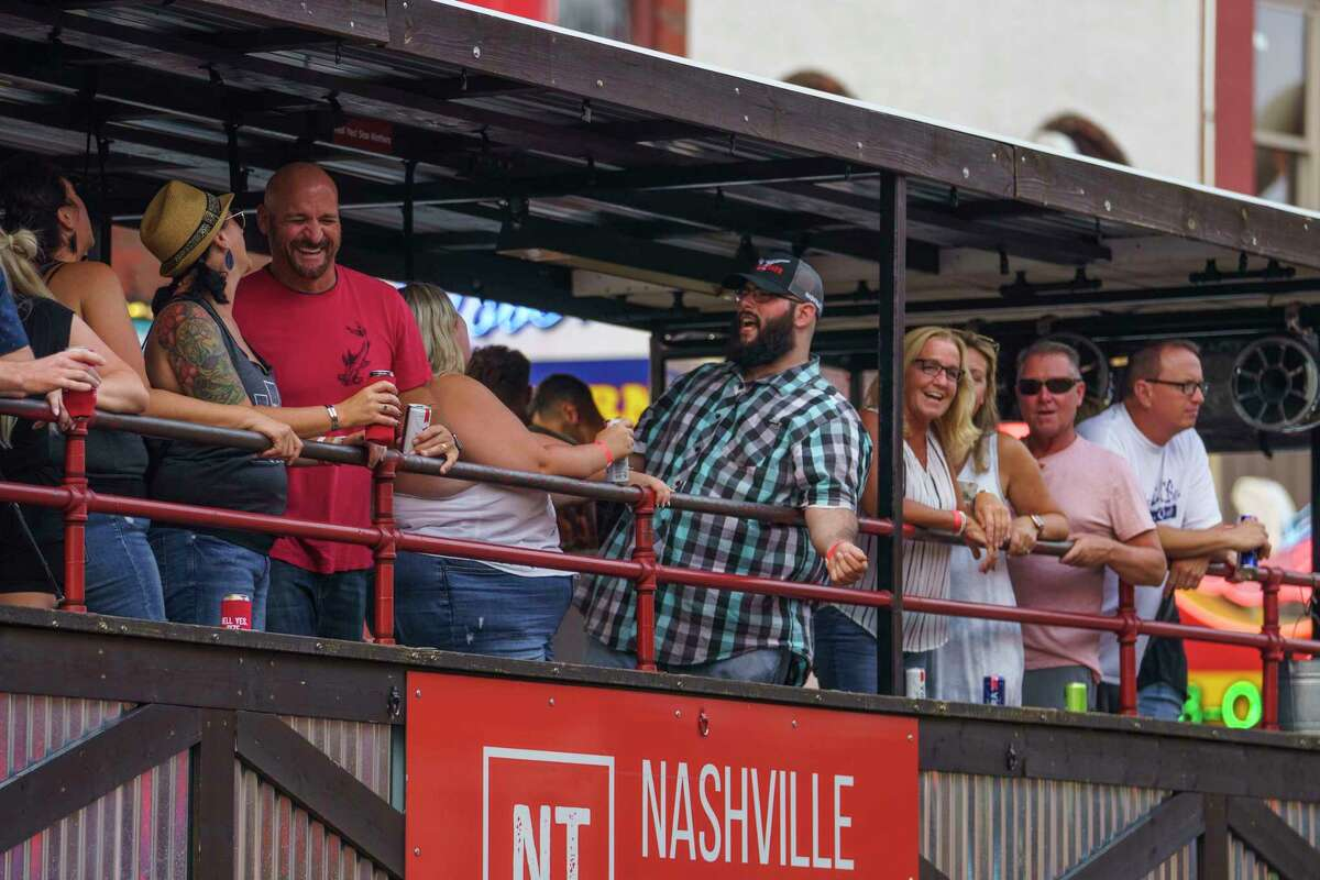 People ride the Nashville Tractor up Broadway in downtown Nashville on Wednesday.