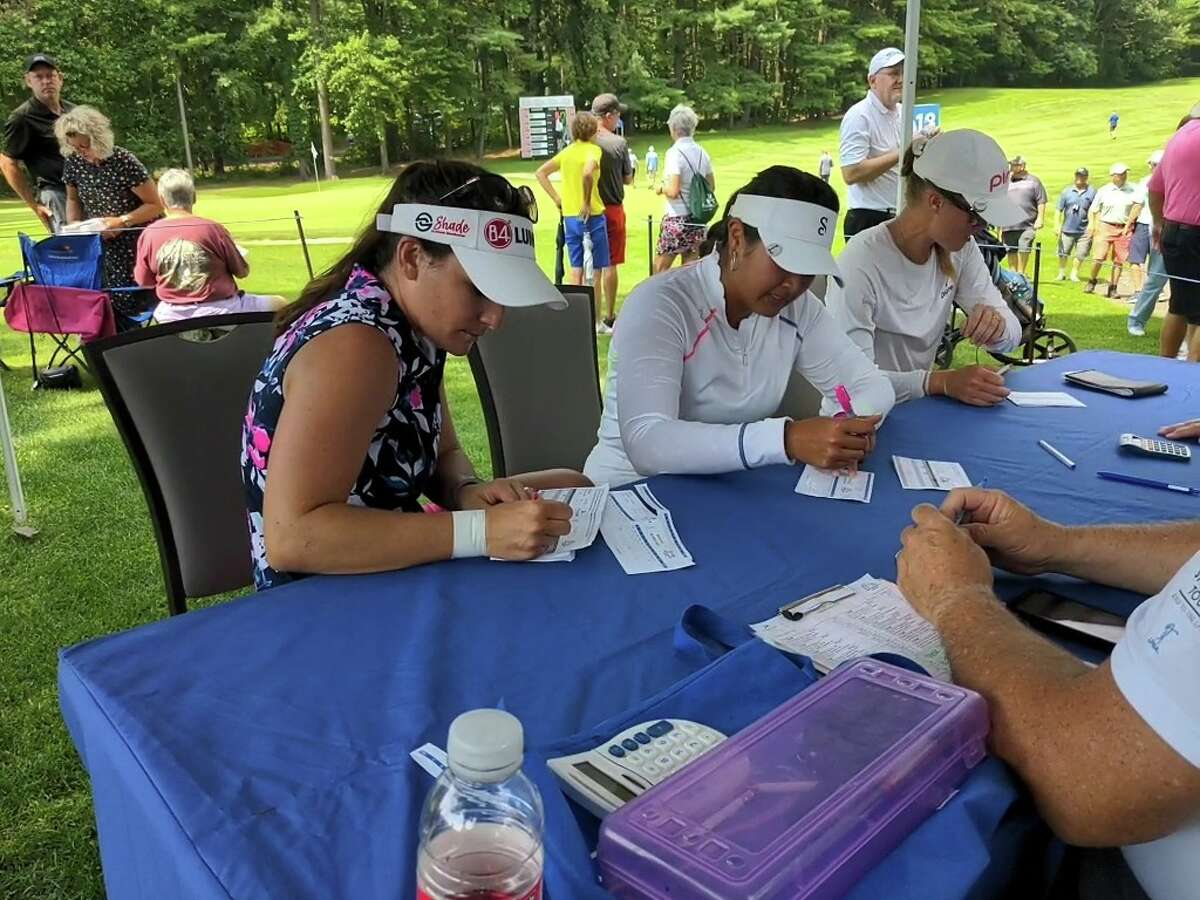 The final group in the Twin Bridges Championship sign their scorecards July 25, 2021, after the final round at the Pinehaven Country Club in Guilderland. From left, runner-up Rachel Rohanna of Marianna, Pa.; winner Lilia Vu of Fountain Valley, Calif., and fourth-place Maddie McCrary of Wylie, Texas. (Pete Dougherty/Times Union)