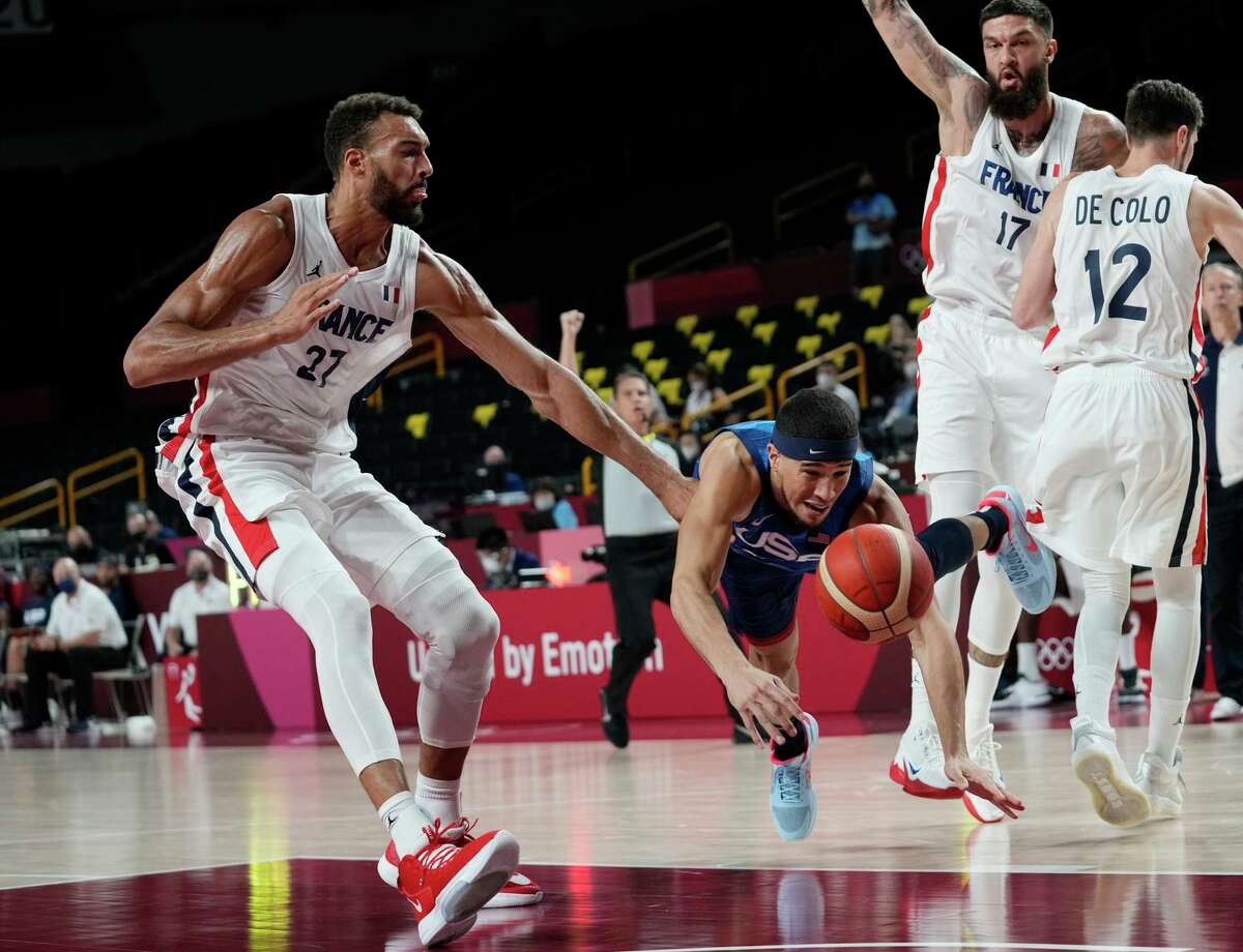 U.S. guard Devin Booker (center) falls as he is fouled by France's Rudy Gobert (27) during a preliminary game.