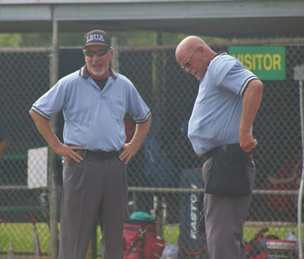 Umpires Tim Mooren (left) and Robert Nolen have one of their discussions between innings at a recent youth game. A common sight at local ballfields, they'll be in Louisiana this weekend for the Mustang (10U) World Series.