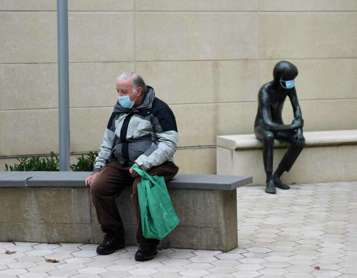 Greenwich's Earl Coyne wears a mask while waiting to pick up a book beside the beloved sculpture known as Andre, also wearing a mask, outside the Greenwich Library in Greenwich, Conn. Tuesday, Nov. 17, 2020.
