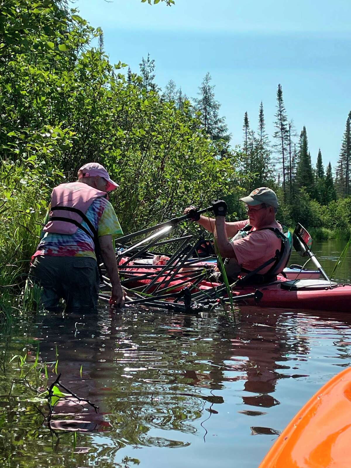 Volunteers wrestle to haul a large tent out of the Platte River during the Clean Sweep event on July 17. (Courtesy Photo)