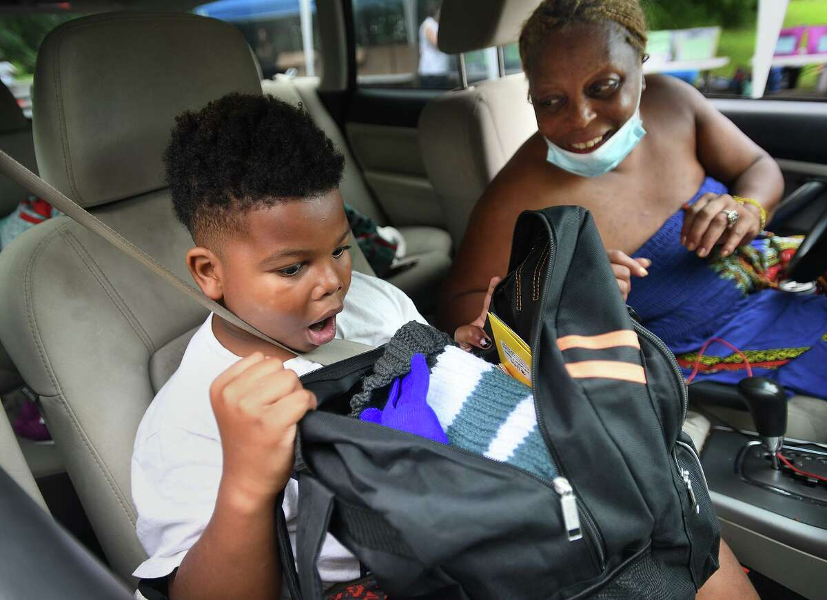 Fifth grader William Breuer, 9, is excited to open his new backpack with his mom, Nichole Justice, during the annual Back to School Shop drive-thru distribution at Davenport Ridge Elementary School in Stamford on Sunday.