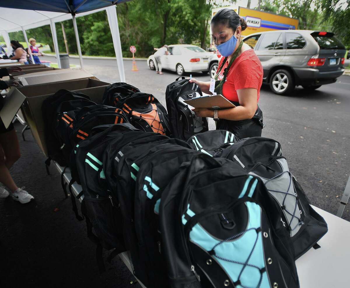 Volunteer Alicia Ochoa picks out a backpack to fill to a child's specifications during the annual Back to School Shop drive-through distribution at Davenport Ridge Elementary School in Stamford, Conn. on Sunday, July 25, 2021 .