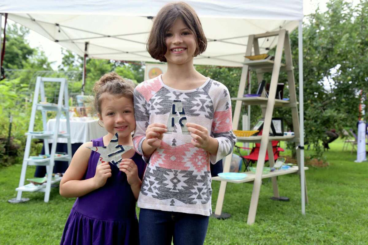 Mariam Carr, 4, of Fairfield, and her sister, Aliya, 8, show off the presents given by Fairfield artist Stephen Goldstein at the Eco Market at Wakeman Town Farm on Sunday, July 25, 2021, in Westport, Conn.