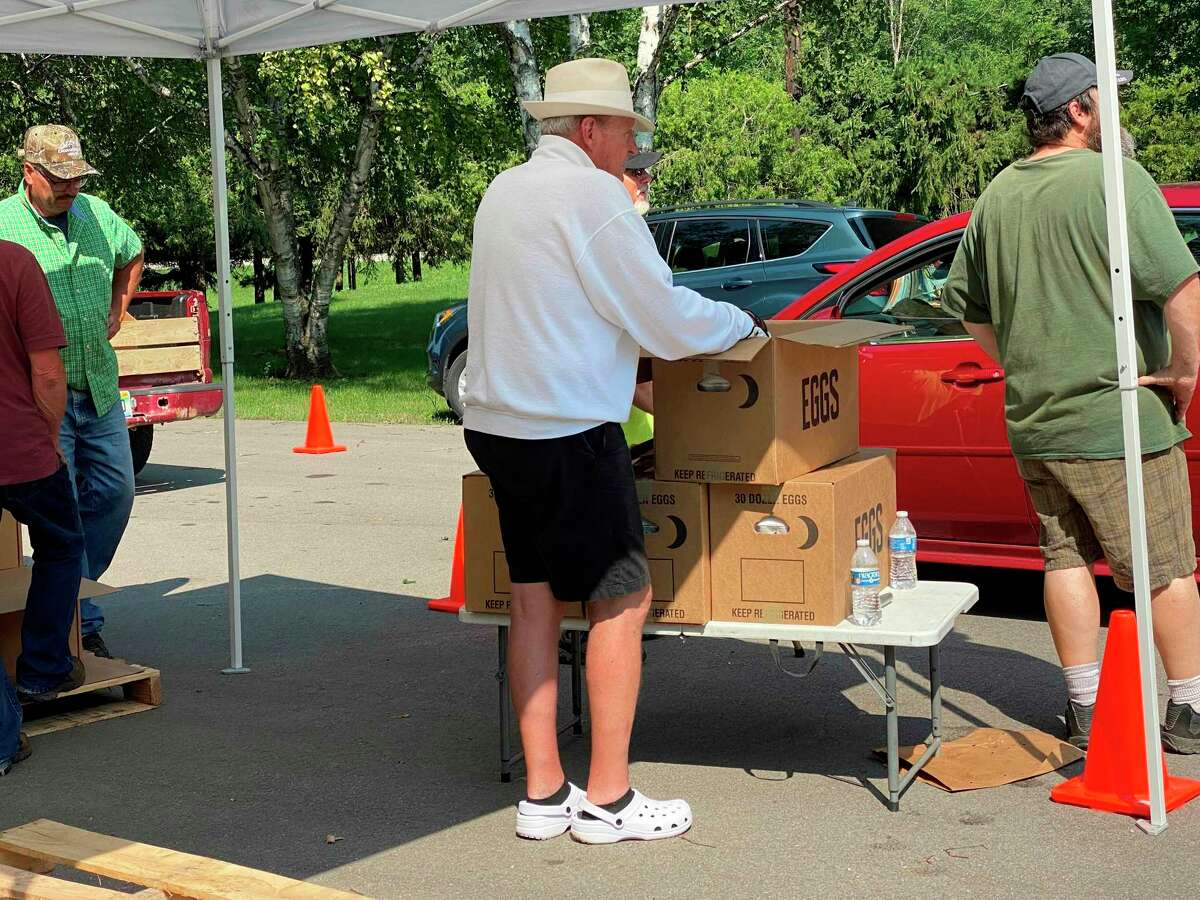 Volunteers pass out eggs and milk during a recent drive-thru food pantry held at the Ubly Fox Hunters Club. (Mark Birdsall/Huron Daily Tribune)