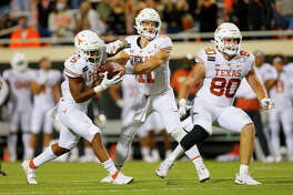 Quarterback Sam Ehlinger #11 hands the ball to running back Bijan Robinson #5 of the Texas Longhorns for a two-yard effort against the Oklahoma State Cowboys in overtime at Boone Pickens Stadium on October 31, 2020 in Stillwater, Oklahoma. Texas won 41-34 in overtime.