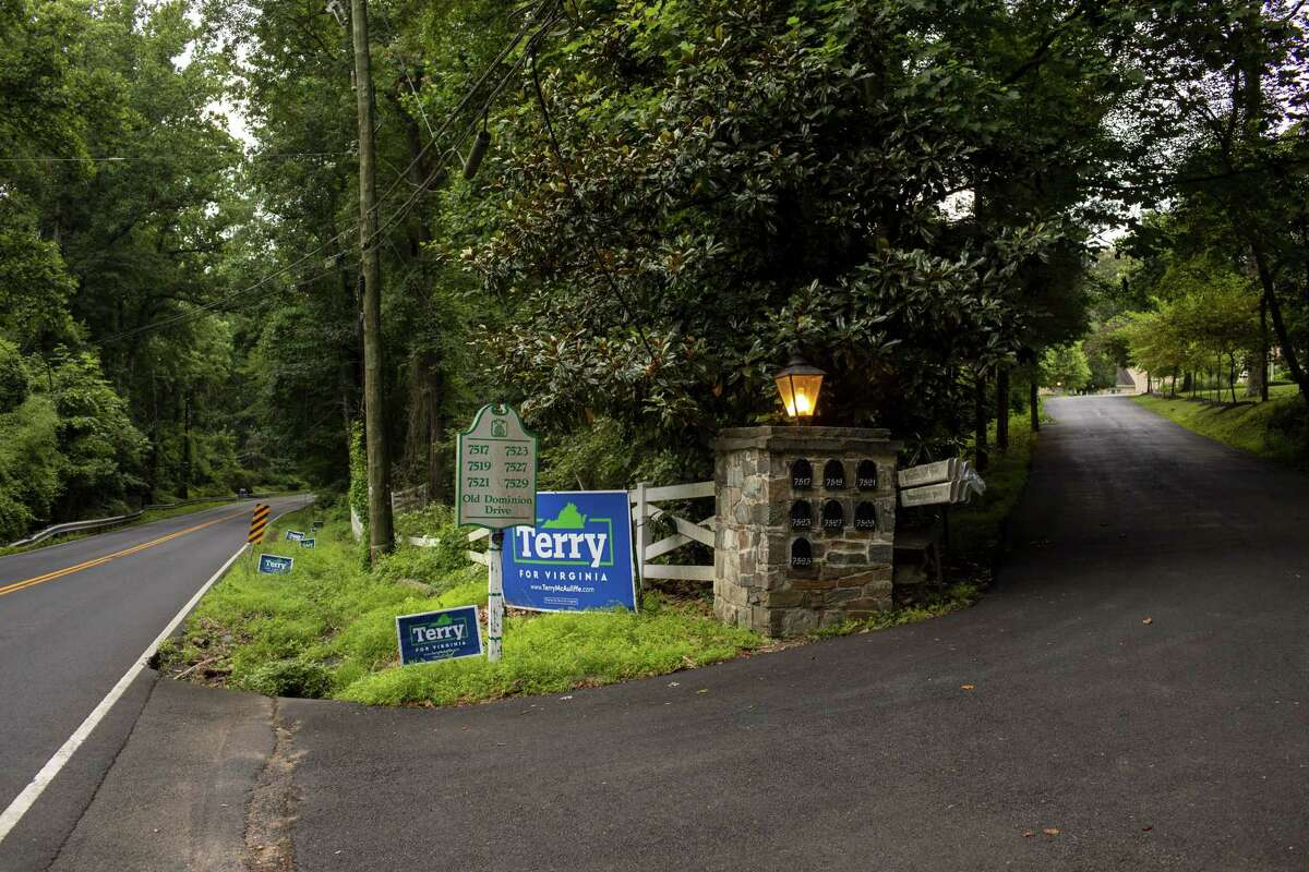 Campaign signs stand along Old Dominion Rd. near the entrance of the neighborhood where Virginia gubernatorial candidate Terry McAuliffe lives in McLean, Va. on July 11, 2021.