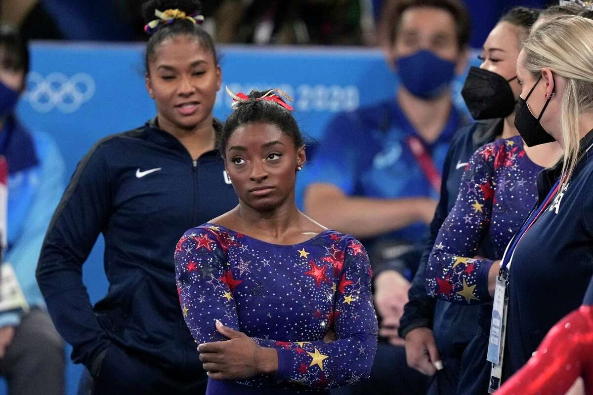 Simone Biles, of the United States, waits for her score after performing on the balance beam during the women's artistic gymnastic qualifications at the 2020 Summer Olympics, Sunday, July 25, 2021, in Tokyo.
