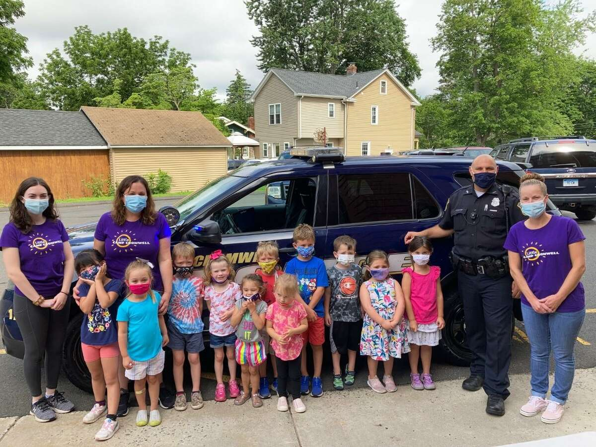 """Cromwell Police Officer Peter A. Pietraroia recently visited the town's Little Camp program to celebrate Cromwell Spirit Week. The school resource officer read a story to children, handed out police """"badges"""" and allowed each child to sit in the driver's seat of his cruiser."""