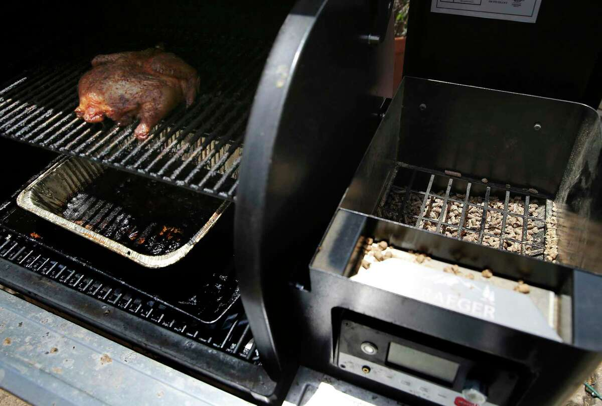A chicken cooks on a Traeger Timberline 850 model pellet cooker.