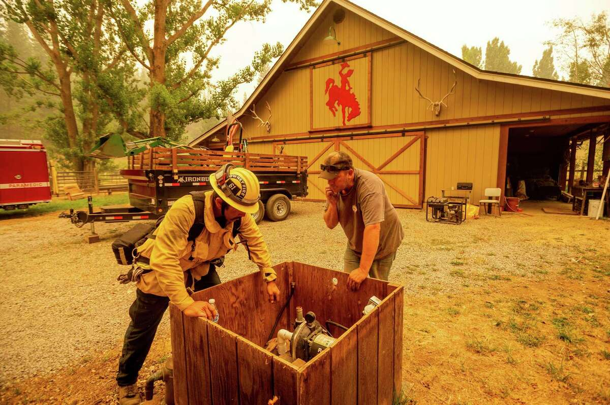 Jesse Ackley and firefighter Sergio Zavala examine a water pump Sunday while preparing for the Dixie Fire's approach in Plumas County. Officials expanded evacuation orders earlier in the day.