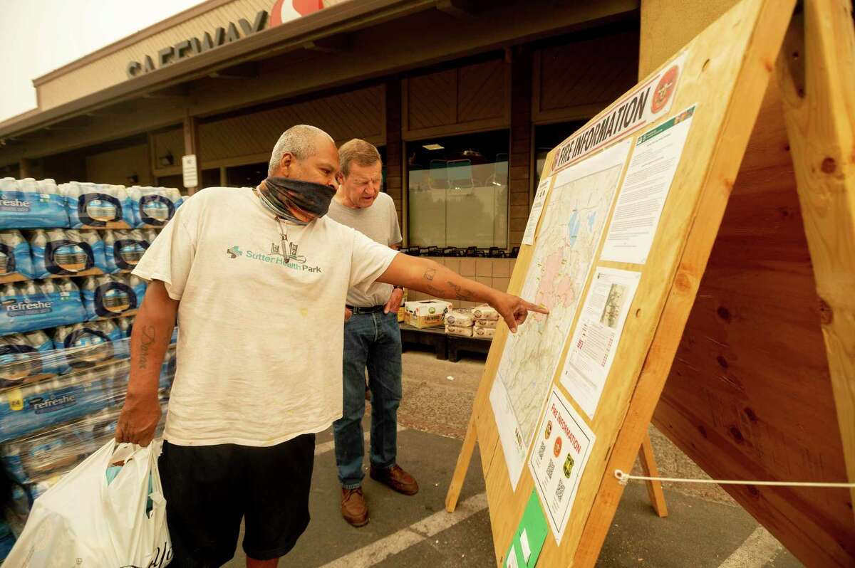 As new evacuation orders take effect for the Dixie Fire, Carlos Duran (left) and Rich McFeely examine a fire map Sunday in Quincy (Plumas County).