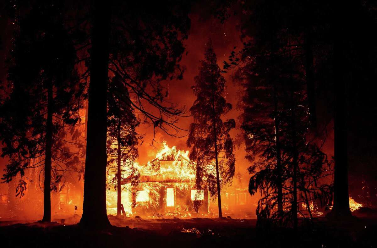 A home burns Saturday as flames from the Dixie Fire tear through the Indian Falls neighborhood of unincorporated Plumas County.