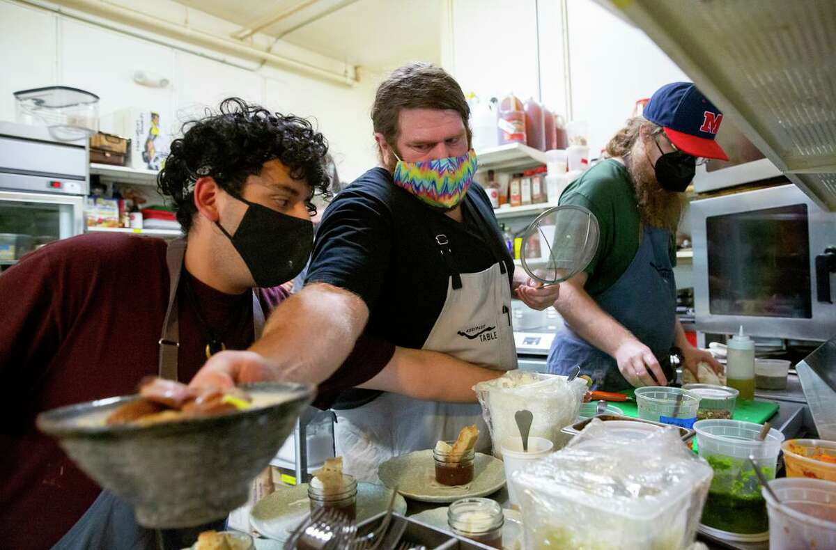 Andrew Greene, co-owner of Abstract Table, works with line cook Jessie Romero (left) and sous chef Will Crosby (right) in the restaurant's kitchen.