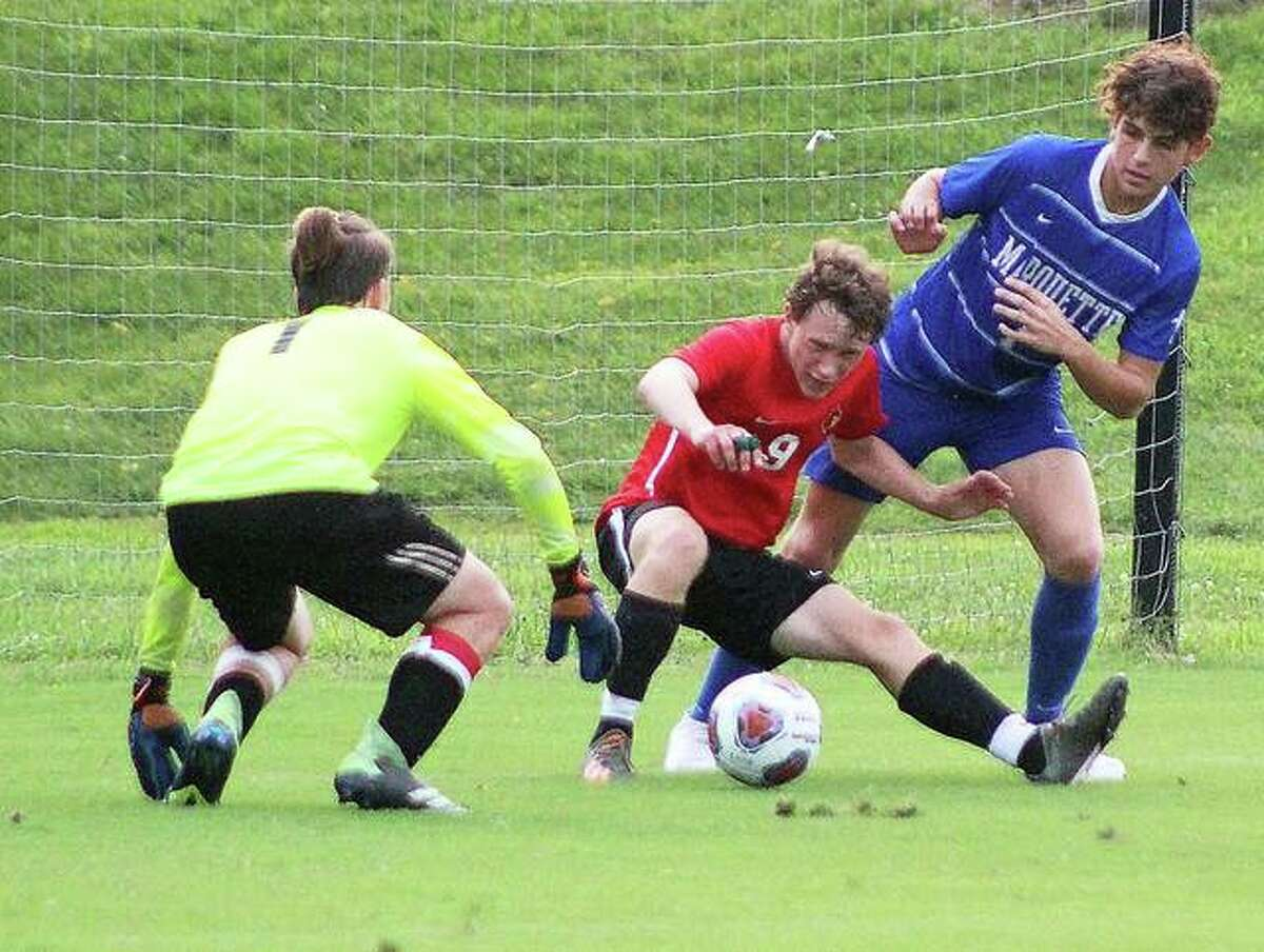 Alton goalie Aiden Belchick, left and Jacob Larson, center, battle for the ball, along with Marquette Myles Paniagua, during the summer soccer jamboree Sunday evening at Principia College in Elsah.