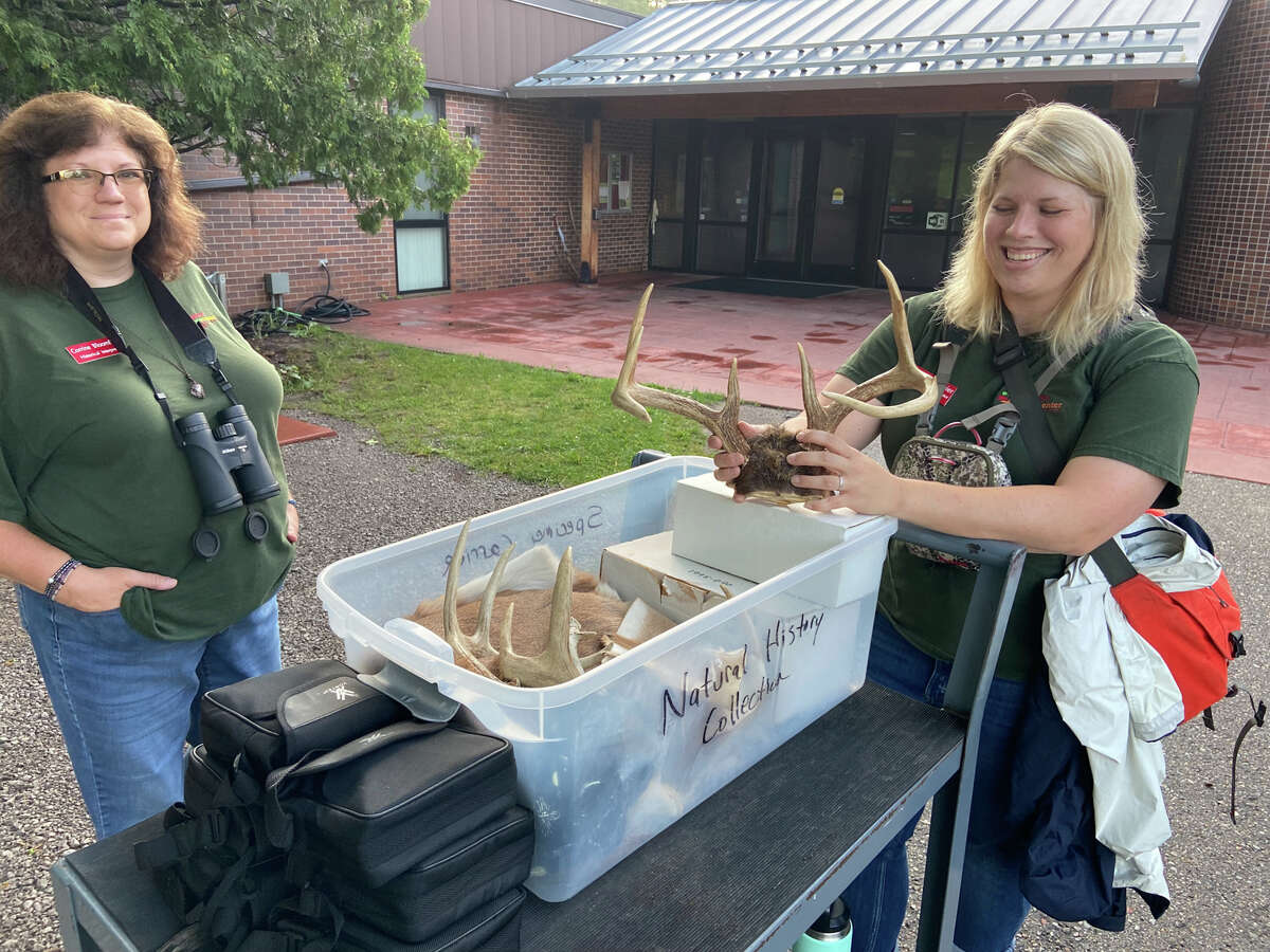 Michelle Fournier, right, displays antlers during the Full Moon Walk at 8p.m. July 24 at the Chippewa Nature Center.
