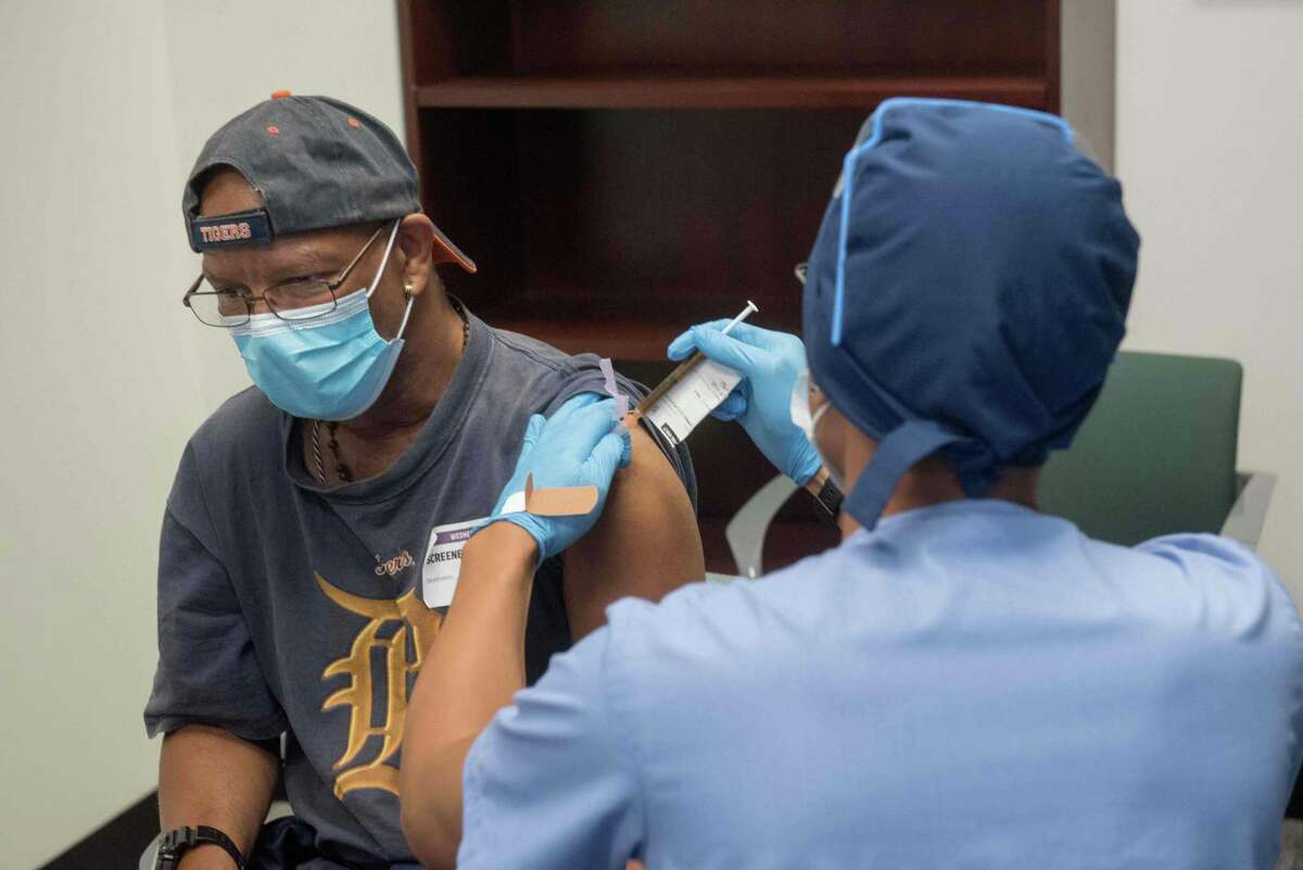 A man receives a COVID-19 vaccine in Detroit in August. Early in the pandemic, it was clear COVID-19 was taking a greater toll on minorities, particularly African Americans and Latinos. A new report shows a dramatic gap in life expectancy.