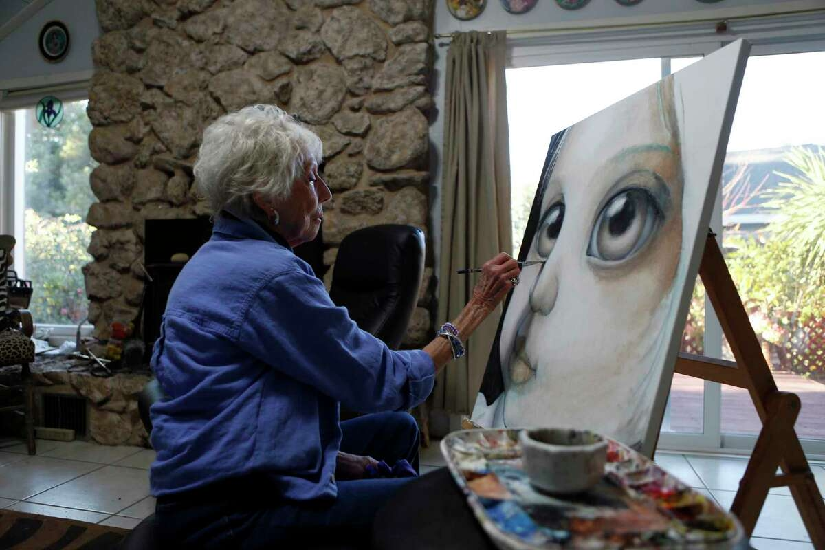 """Painter Margaret Keane, creator of the famous Big Eye paintings of waifs originally credited to her late former husband, Walter, and the subject of Tim Burton's film, """"Big Eyes"""", paints at her residence in Napa, Calif., on Tuesday, November 25, 2014."""