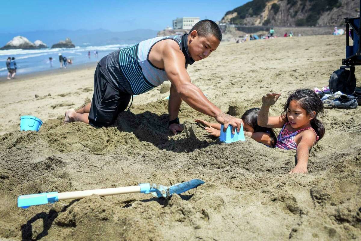 Tyrone Keller of Sacramento and his daughters, Nayeli Keller (right), age 9, and Mia Keller (second from right), age 4, play in the sand at Ocean Beach in San Francisco, Calif. on Monday, May 31, 2021.